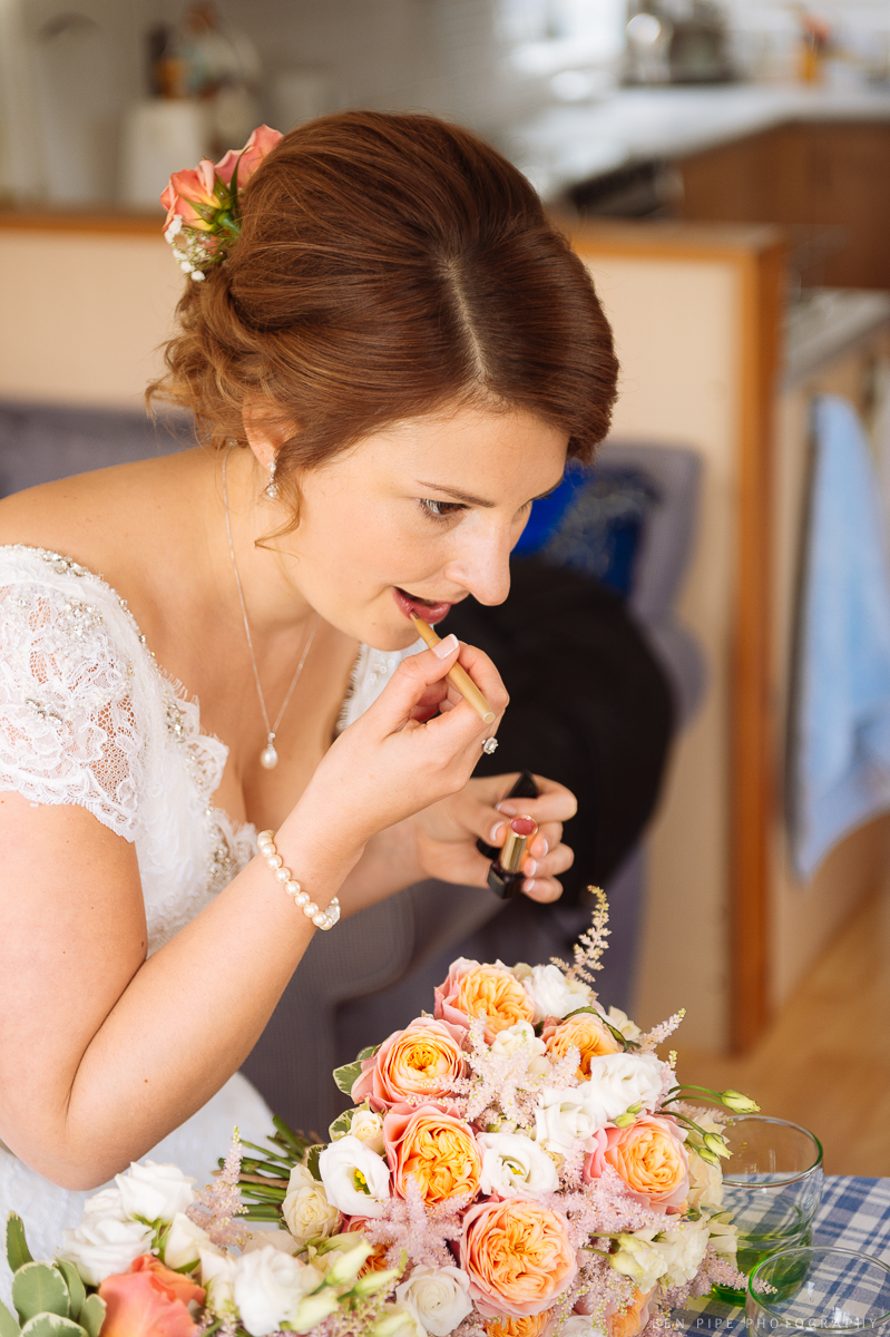 bride applying lipstick before wedding